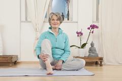 A senior woman sitting on an exercise mat Stock Photos
