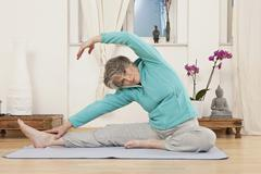 A senior woman stretching in a yoga studio - stock photo