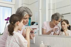 A grandmother teaching her granddaughter how to brush teeth - stock photo