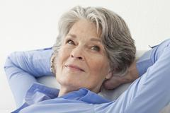 A senior woman relaxing with her hands behind her head Stock Photos