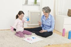 A grandmother and her granddaughter finger painting - stock photo