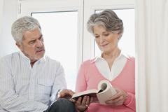 A senior couple looking at a book Stock Photos
