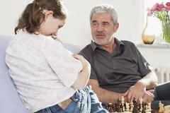 A grandfather and his granddaughter playing chess - stock photo