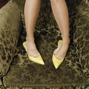 Detail of a woman wearing high heel shoes and standing on an arm chair Stock Photos