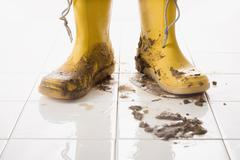 A pair of muddy rubber boots - stock photo