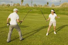 Two golfers sparring with golf clubs - stock photo