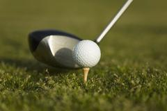 Detail of a golf club next to a golf ball on a tee Stock Photos