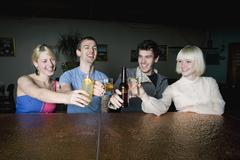 Four friends toasting drinks at a bar Stock Photos