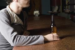 A man sitting at a bar with a bottle of beer - stock photo