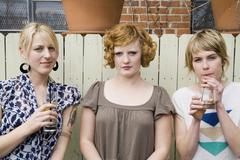 Three young woman standing in front of a fence - stock photo