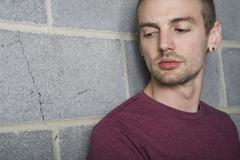 A young man leaning against a brick wall and looking away Stock Photos