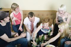 Joukko ystäviä syöminen ja juominen olohuoneessa Kuvituskuvat