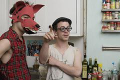 Two young men standing in a kitchen wearing silly disguises - stock photo
