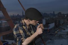 A young man standing on a fire escape lighting a cigarette Stock Photos