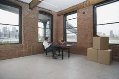 Couple sitting in an empty loft apartment Stock Photos