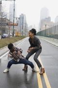 A young couple play fighting on a street, Manhattan, New York City - stock photo