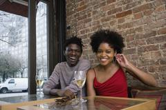 Stock Photo of A young couple sitting in a restaurant with glasses of white wine