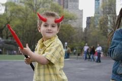 A young boy wearing devils horns and holding a pitchfork, Central Park, New York - stock photo
