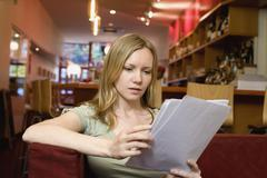 A young woman sitting in a cafe and looking at the menu Stock Photos