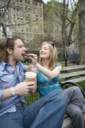 A woman feeding a man a cookie in a park, Central Park, New York City Stock Photos