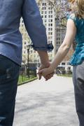A young couple holding hands in a park, Central Park, New York City Stock Photos