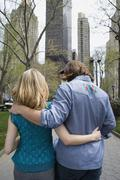 A young couple walking arm in arm through a city park, Central Park, New York Stock Photos