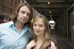 Portrait of a young couple standing on a city street - stock photo