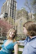 A young couple sitting on a park bench together, Central Park, New York City - stock photo