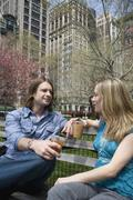 A young couple sitting on a park bench with iced coffees, Central Park, New York - stock photo