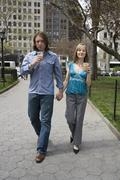 Stock Photo of A young couple walking through a city park holding hands, Central Park, New York