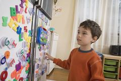 A young boy looking at toy magnets on a refrigerator door Stock Photos