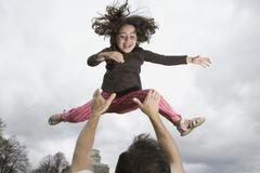 A father throwing his daughter into the air Stock Photos