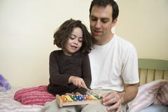 Nuori tyttö istuu isänsä kanssa ja pelaa ksylofoni Kuvituskuvat