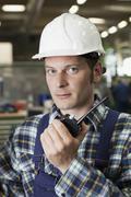 Portrait of a factory worker holding a walkie-talkie Kuvituskuvat
