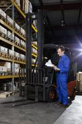 A manual worker looking at a checklist in a metal parts warehouse Stock Photos