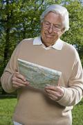 A senior man looking at a map, outdoors Stock Photos