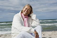 A senior woman sitting on a beach - stock photo
