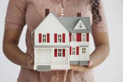 Midsection of a woman holding a miniature house Stock Photos