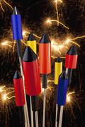 Rocket firecrackers with a firework display behind them Stock Photos