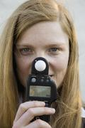 Stock Photo of A woman holding a light meter in front of her face