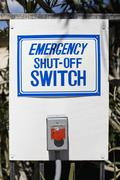 An EMERGENCY SHUT-OFF SWITCH sign and button Stock Photos