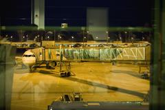 A passenger boarding bridge connected to an airplane Stock Photos