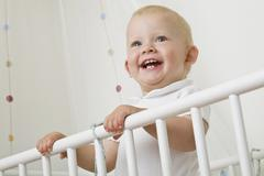 A toddler standing in a baby crib Stock Photos
