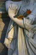 Detail of a statue adorned with roses - stock photo