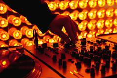 A DJ adjusting levels on a sound mixer at a nightclub Stock Photos