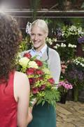 A woman buying a bouquet in a florists - stock photo