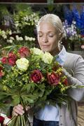 A woman smelling a bouquet of flowers in a florists Stock Photos
