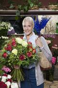 Stock Photo of A woman holding a bouquet of roses in a florists