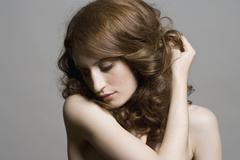 Portrait of a woman holding her hair back Stock Photos