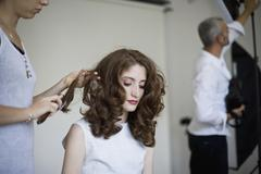 A model having her hair prepared - stock photo